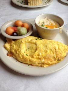 Seafood Omelet with andouille, fresh fruit & cheee grits